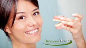 denture relines toronto woman smiling holding up dentures